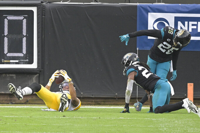 Pittsburgh Steelers wide receiver Chase Claypool, left, holds up the ball after making a touchdown reception in front of Jacksonville Jaguars cornerback Chris Claybrooks, center, and safety Jarrod Wilson during the first half of an NFL football game, Sunday, Nov. 22, 2020, in Jacksonville, Fla. (AP Photo/Phelan M. Ebenhack)