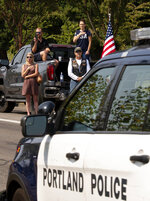 People look on during a procession to a memorial service for Clark County Sheriff's Detective Jeremy Brown, Tuesday, Aug. 3, 2021, from Clark College, Vancouver, Wash. Brown was fatally shot July 23 while on duty. Hundreds of law enforcement vehicles drove in the procession up I-5 to ilani Casino in La Center, Wash. (Joshua Hart/The Columbian via AP)