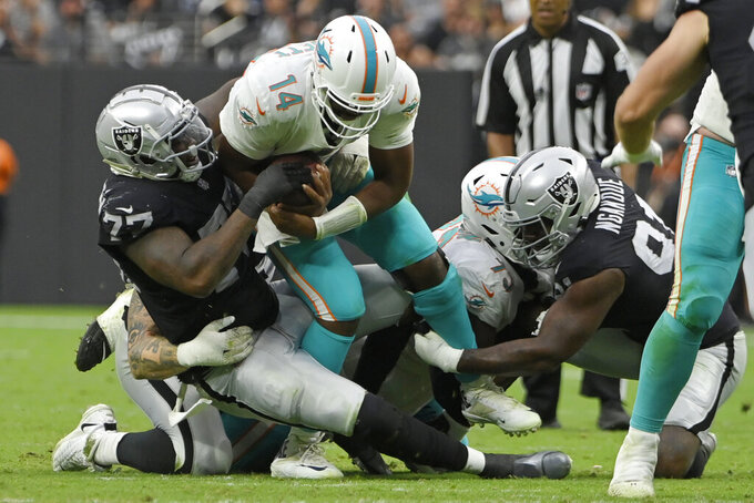 Las Vegas Raiders defensive end Quinton Jefferson (77) tackles Miami Dolphins quarterback Jacoby Brissett (14) during the second half of an NFL football game, Sunday, Sept. 26, 2021, in Las Vegas. (AP Photo/David Becker)