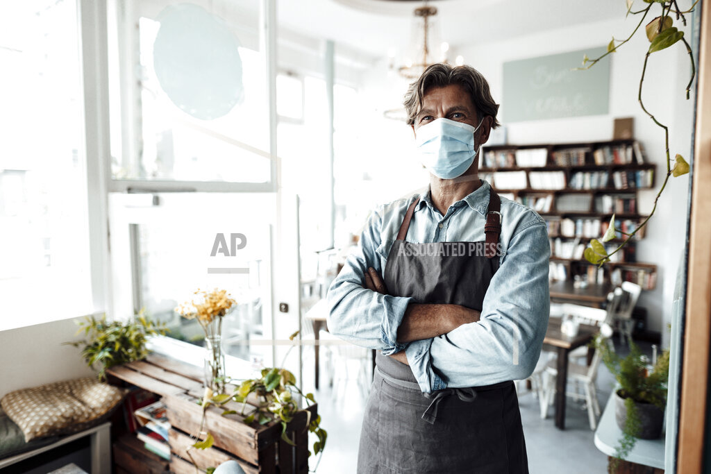 Male cafe owner wearing protective face mask standing with arms crossed
