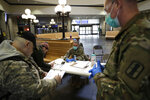 Members of the Rhode Island National Guard, right, provide passengers with a questionnaire and advised them to self-quarantine for 14 days if arriving from out of state, as they disembark from a train, Monday, March 30, 2020, at Providence Station train station, in Providence, R.I. The new coronavirus causes mild or moderate symptoms for most people, but for some, especially older adults and people with existing health problems, it can cause more severe illness or death. (AP Photo/Steven Senne)