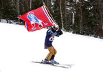 A fan of the New England Patriots NFL football team skis with a team flag at the Sugarloaf ski resort, Sunday, Feb. 3, 2019, in Carrabassett Valley, Maine. About 200 skiers took part to show their support for the Patriots prior to today's Super Bowl game against the Los Angeles Rams. (AP Photo/Robert F. Bukaty)