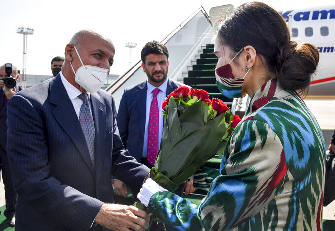 Afghan President Ashraf Ghani, left, receives a bunch of flowers from a woman upon his arrival at Tashkent International airport, Uzbekistan, Thursday, July 15, 2021. Uzbekistan's President Shavkat Mirziyoyev, Afghan President Ashraf Ghani and Pakistan's Prime Minister Imran Khan are among those expected to attend the conference along with foreign ministers of Central and South Asian nations, according to Mirziyoyev's official website. (AP Photo)