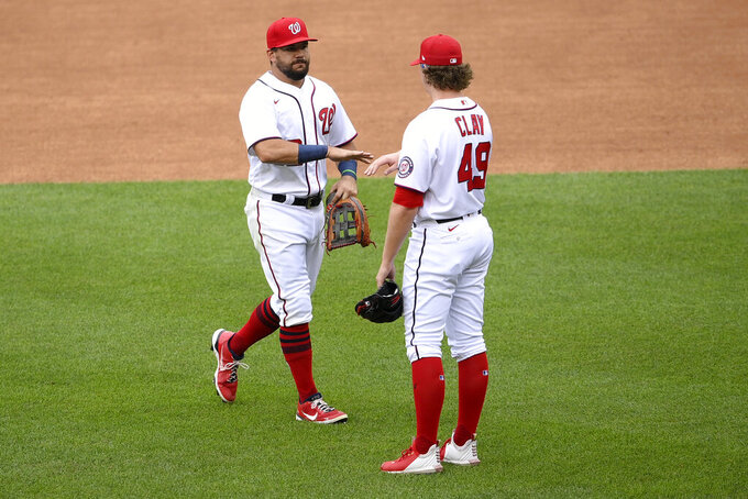 Washington Nationals' Kyle Schwarber, left, and Sam Clay celebrate after a baseball game against the San Francisco Giants, Sunday, June 13, 2021, in Washington. The Nationals won 5-0.(AP Photo/Nick Wass)