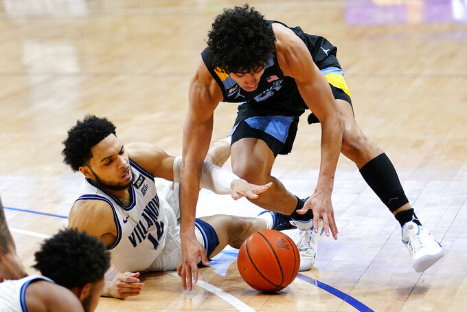 Marquette's D.J. Carton, right, and Villanova's Caleb Daniels chase after a loose ball during the second half of an NCAA college basketball game, Wednesday, Feb. 10, 2021, in Villanova, Pa. (AP Photo/Matt Slocum)
