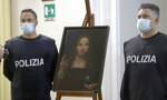 """In this image taken  from a video, two police officers pose by a copy of the """"Salvator Mundi"""" (Savior of the World), by Leonardo da Vinci, in Naples, Italy, Wednesday, Jan. 20, 2021. Italian police have recovered a copy of Leonardo da Vinci's 16th century """"Salvator Mundi"""" painting of Jesus Christ that was stolen from a Naples church without the priests even realizing it was gone. The discovery was made over the weekend when Naples police working on a bigger operation found the painting hidden in an apartment. Police chief Alfredo Fabbrocini said the owner offered a """"less than credible"""" explanation that he had """"casually"""" bought it at a small market. (AP Photo/Sicomunicazione)"""