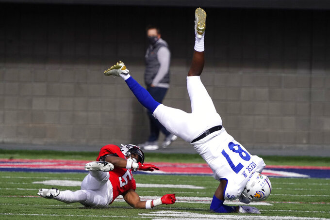 Ball State safety Bryce Cosby upends San Jose State tight end Derrick Deese Jr. (87) in the first half of the Arizona Bowl NCAA college football game, Thursday, Dec. 31, 2020, in Tucson, Ariz. (AP Photo/Rick Scuteri)