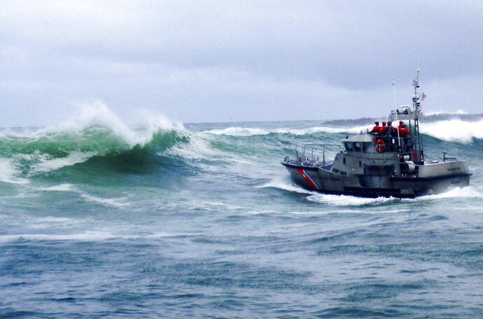 In this Tuesday, Jan. 8, 2019 photo, provided by the U.S. Coast Guard, a U.S. Coast Guard boat crew responds to three fishermen in the water after the commercial fishing vessel Mary B II capsized while crossing Yaquina Bay Bar off the coast of Newport, Ore. Authorities say three men were killed when their fishing boat capsized in rough waters off the Oregon coast. (U.S. Coast Guard via AP)