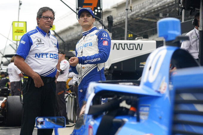 Alex Palou, second from left, of Spain, talks with a crew member before a practice session for a IndyCar auto race at Indianapolis Motor Speedway, Friday, Aug. 13, 2021, in Indianapolis. (AP Photo/Darron Cummings)