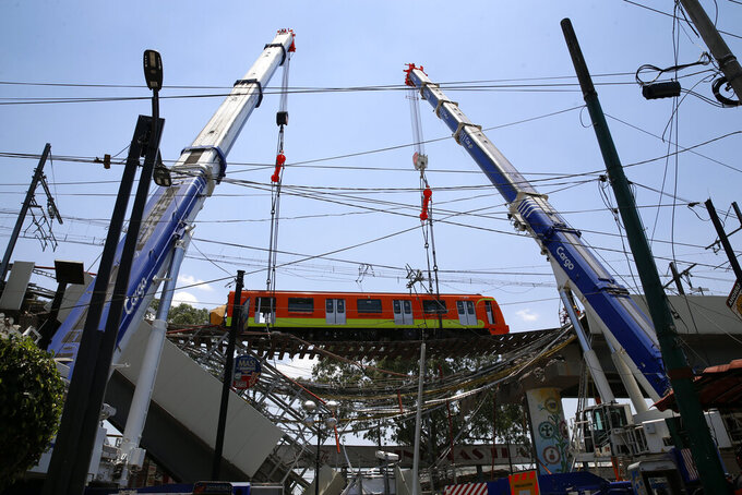 A subway car is prepared to be lowered to the ground, with the help of cranes, from a collapsed elevated section of the metro, in Mexico City, Tuesday, May 4, 2021. The elevated section of the Line 12 metro collapsed late Monday, killing at least 23 people and injuring at least 79, city officials said. (AP Photo/Marco Ugarte)