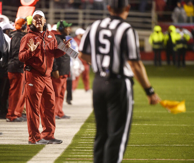 Arkansas coach Chad Morris talks with an official after a penalty during the first half of the team's NCAA college football game against Mississippi on Saturday, Oct. 13, 2018, in Little Rock, Ark. (AP Photo/Michael Woods)
