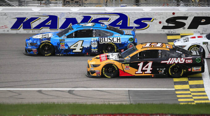 Kevin Harvick (4) and Clint Bowyer (14) head past the start-finish line to begin the NASCAR Cup Series auto race at Kansas Speedway in Kansas City, Kan., Saturday, May 11, 2019. (AP Photo/Orlin Wagner)