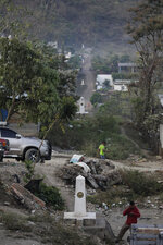 A line of markers indicates the border between La Mesilla, Guatemala, left, and Las Champas Mexico, two towns that sit side by side on Mexico's southern border, Tuesday, March 23, 2021. (AP Photo/Eduardo Verdugo)