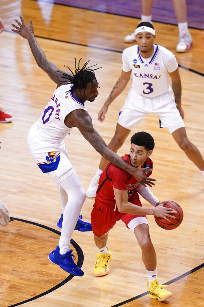 Eastern Washington guard Michael Meadows, right, looks for help as Kansas guard Marcus Garrett (0) pressures during the first half of a first-round game in the NCAA college basketball tournament at Farmers Coliseum in Indianapolis, Saturday, March 20, 2021. (AP Photo/AJ Mast)