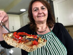 Tiziana di Costanzo, co-founder of Horizon Insects, holds up a slice of pizza made with cricket powder, in her London kitchen on June 2, 2021. While insects are commonly eaten in parts of Asia and Africa, they're increasingly seen as a viable food source in the West as Earth's growing population puts more pressure on global food production. Experts say they're rich in protein, yet can be raised much more sustainably than beef or pork. Regulatory change has also made things easier for European companies looking to market insects directly to consumers. (AP Photo/Kelvin Chan)
