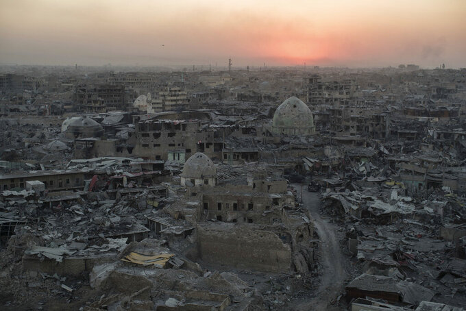 FILE - In this July 11, 2017 file photo, the sun sets behind destroyed buildings in the west side of Mosul, Iraq. The 9-month fight to defeat the Islamic State group in Mosul ended in a crescendo of devastation: bombardment that damaged or destroyed a third of its historic Old City in just three weeks. The cost of uprooting the militants was the destruction of large swaths of Iraq's second largest city, leaving a population that is displaced, exhausted and potentially embittered if there is no reconstruction. (AP Photo/Felipe Dana)