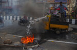 Police clear road blocks as a man tries to douse a fire set by protestors in Gauhati, India, Thursday, Dec. 12, 2019. Police arrested dozens of people and enforced a curfew Thursday in several districts in India's northeastern Assam state where thousands protested legislation that would grant citizenship to non-Muslims who migrated from neighboring countries. (AP Photo/Anupam Nath)
