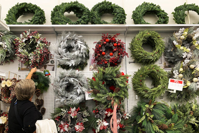 FILE - In this Nov. 9, 2019, file photo a woman looks through holiday wreathes on sale at a retail store during in Pembroke Pines, Fla. On Tuesday, Nov. 26, the Conference Board reports on U.S. consumer confidence for November. (AP Photo/Brynn Anderson, File)