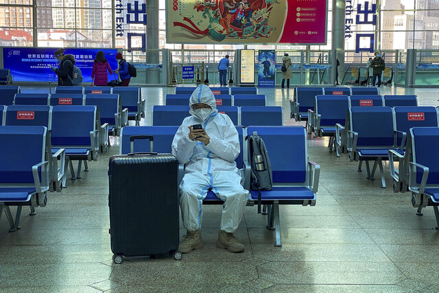 A traveller wearing protective gear to help curb the spread of the coronavirus sits alone on the bench as he waits for his train at the South Train Station in Beijing, Thursday, Jan. 28, 2021. Efforts to dissuade Chinese from traveling for Lunar New Year appeared to be working. Beijing's main train station was largely quiet on the first day of the travel rush and estimates of passenger totals were smaller than in past years. (AP Photo/Andy Wong)