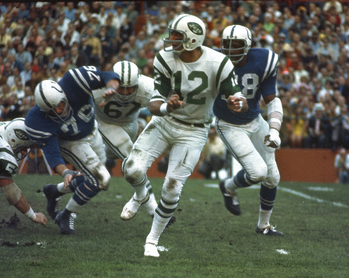 FILE - In this Jan. 12, 1969, file photo, New York Jets quarterback (12) Joe Namath gets off a pass under pressure from the Baltimore Colts defenders during Super Bowl III in Miami, Fla. Namath will be in the building Sunday, and so will the rest of the only Super Bowl-winning Jets team. It's the 50-year anniversary of that squad, and rookie quarterback Sam Darnold will take on the Indianapolis Colts _ the same franchise that was stunned by New York in that historic game. (AP Photo/File)