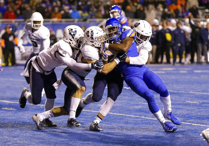 Boise State running back Alexander Mattison (22) is wrapped up by the Utah State defense in the second of an NCAA college football game, Saturday, Nov. 24, 2018, in Boise, Idaho. (AP Photo/Steve Conner)