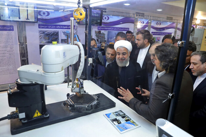 FILE - In this April 9, 2018 file photo, released by an official website of the office of the Iranian Presidency, President Hassan Rouhani listens to explanations on new nuclear achievements at a ceremony to mark