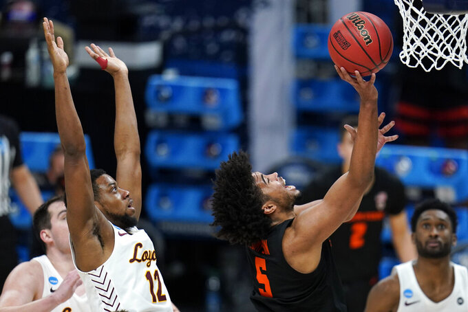 Oregon State guard Ethan Thompson (5) drives to the basket ahead of Loyola Chicago guard Marquise Kennedy (12) during the second half of a Sweet 16 game in the NCAA men's college basketball tournament at Bankers Life Fieldhouse, Saturday, March 27, 2021, in Indianapolis. (AP Photo/Jeff Roberson)