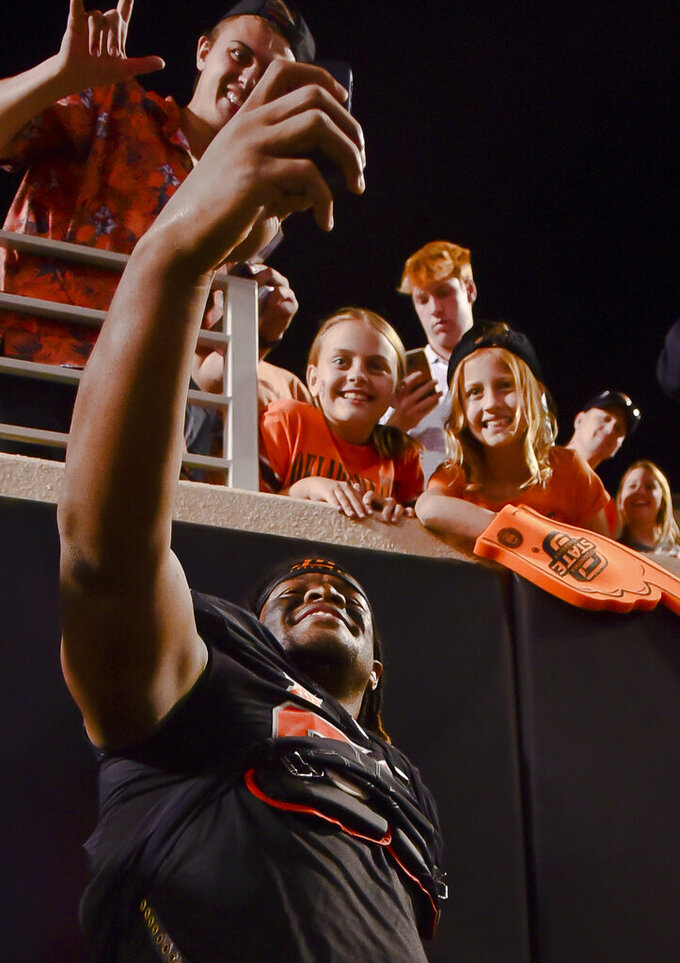 Oklahoma State defensive end Tyler Lacy (89) takes a selfie photo with fans following an NCAA college football game Saturday, Sept. 25, 2021, in Stillwater, Okla. (AP Photo/Brody Schmidt)