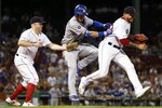Boston Red Sox's Hector Velazquez, right, interferes with the play at first base by Brock Holt, left, allowing Los Angeles Dodgers' Cody Bellinger, center, to reach during the 12th inning of a baseball game in Boston, Monday, July 15, 2019. (AP Photo/Michael Dwyer)