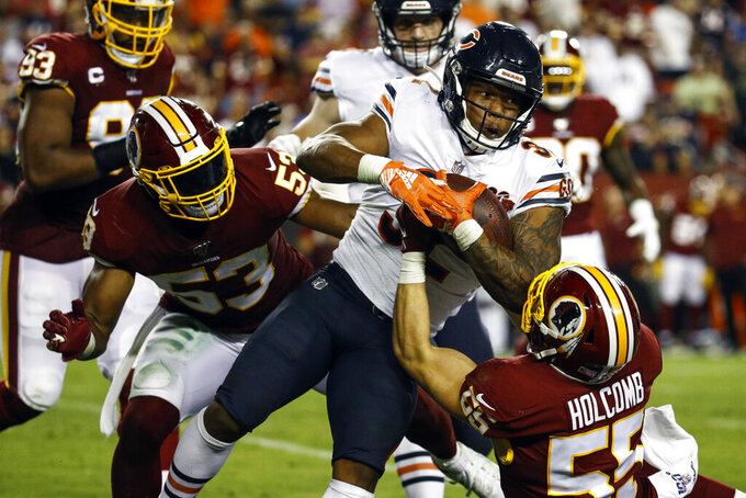 Chicago Bears running back David Montgomery (32) is dragged down by Washington Redskins linebacker Cole Holcomb (55) with help from linebacker Jon Bostic (53) during the second half of an NFL football game Monday, Sept. 23, 2019, in Landover, Md. (AP Photo/Patrick Semansky)