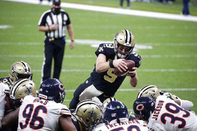 CORRECTS TO NOT A TOUCHDOWN - New Orleans Saints quarterback Drew Brees (9) dives over the pile in the second half of an NFL wild-card playoff football game against the Chicago Bears in New Orleans, Sunday, Jan. 10, 2021. Brees was stopped short of the goal line on fourth down. (AP Photo/Butch Dill)