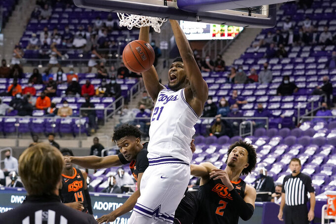 TCU center Kevin Samuel (21) dunks after getting through the defense of Oklahoma State's Matthew-Alexander Moncrieffe, center left, and Cade Cunningham (2) during the second half of an NCAA college basketball game in Fort Worth, Texas, Wednesday, Feb. 3, 2021. (AP Photo/Tony Gutierrez)
