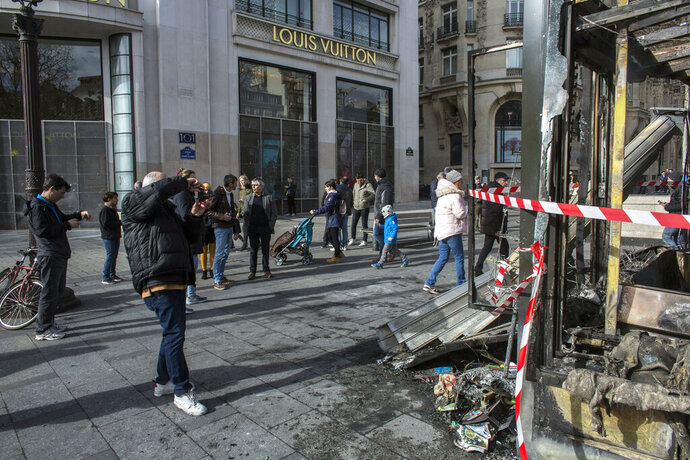 Bystanders take snapshots of the burned out terrasse of the famed restaurant Le Fouquet's on the Champs Elysees the day after it was vandalized and set on fire during the 18th straight weekend of demonstrations by the yellow vests, in Paris, France, Sunday, March 17, 2019. Paris cleaned up one of the world's most glamorous avenues Saturday after resurgent rioting by yellow vest protesters angry at President Emmanuel Macron stunned the nation. (AP Photo/Rafael Yaghobzadeh)