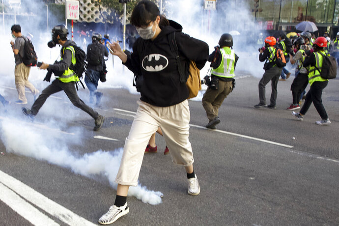 A pro-democracy protester runs away from the tear gas fired by riot police during a rally in Hong Kong, Sunday, Dec. 1, 2019. A huge crowd took to the streets of Hong Kong on Sunday, some driven back by tear gas, to demand more democracy and an investigation into the use of force to crack down on the six-month-long anti-government demonstrations. (AP Photo/Ng Han Guan)