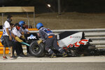 Haas driver Romain Grosjean of France has his car taken after a crash during the Formula One race in Bahrain International Circuit in Sakhir, Bahrain, Sunday, Nov. 29, 2020. (Hamad Mohammed, Pool via AP)