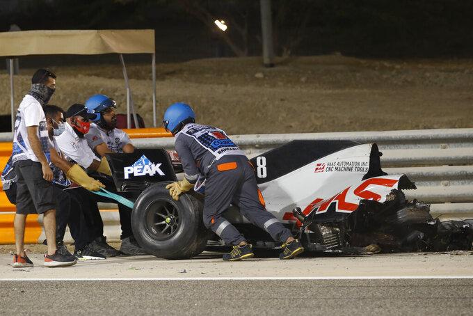 Haas driver Romain Grosjean of France has his car taken after a crash during the Formula One race in Bahrain International Circuit in Sakhir, Bahrain, Sunday, Nov. 29, 2020. (Hamad Mohammed, Pool via AP)