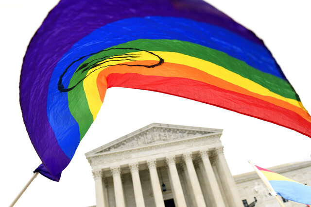 """FILE - In this Oct. 8, 2019, file photo, people gather outside the Supreme Court in Washington. The Supreme Court's Monday ruling shielding LGBT people from employment discrimination dealt a blow to religious conservatives — and was penned by a justice they lauded after his nomination by President Donald Trump. Longtime evangelical conservative leader James Dobson said Tuesday, June 16, 2020 in a statement that what he considers an """"abhorrent decision"""" suggests the nation """"is in the midst of a spiritual war over its very heart and soul."""" (AP Photo/Susan Walsh, File)"""