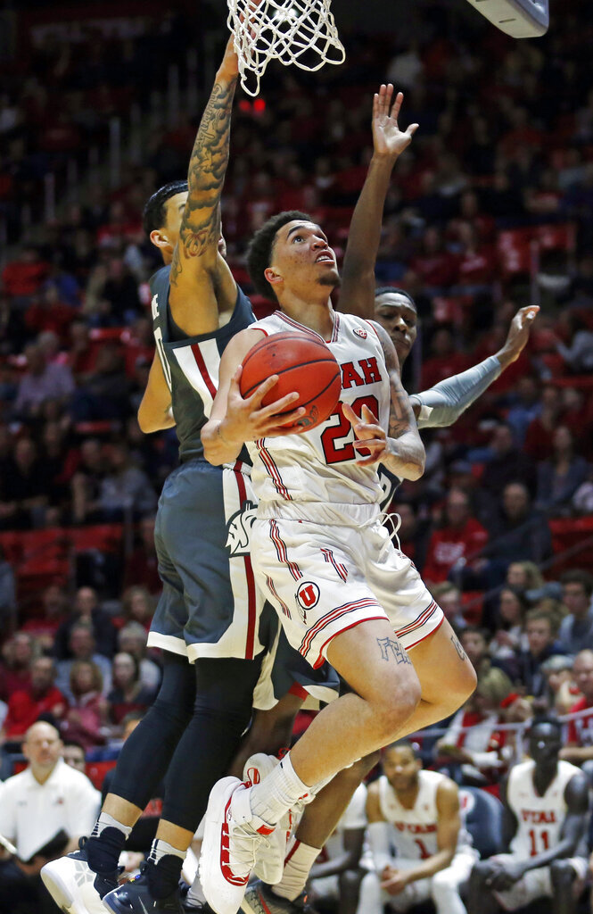 Utah forward Timmy Allen (20) goes to the basket as Washington State's Isaiah Wade, left, and Viont'e Daniels, right, defend during the second half of an NCAA college basketball game Saturday, Jan. 12, 2019, in Salt Lake City. (AP Photo/Rick Bowmer)