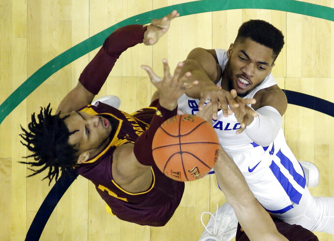 Buffalo's Jayvon Graves, right, and Central Michigan's Romelo Burrell reach for a rebound during the second half of an NCAA college basketball game in the semifinals of the Mid-American Conference men's tournament Friday, March 15, 2019, in Cleveland. Buffalo won 85-81. (AP Photo/Tony Dejak)