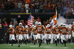 FILE - Texas' Jeffrey McCulloch (23) and Josh Thompson (29) lead the team onto the field before the first half of the NCAA Big 12 Conference football championship against Oklahoma, Saturday, Dec. 1, 2018, in Arlington, Texas. Making predictions for a most unpredictable year is challenging, but everything about playing football is tougher than usual. (AP Photo/Roger Steinman, File)