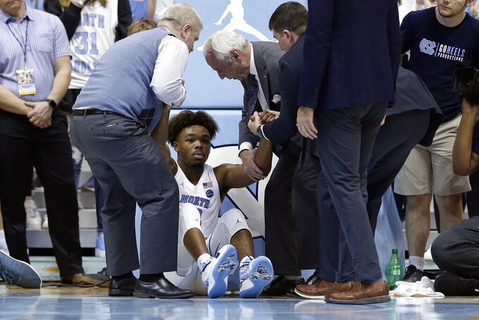 North Carol;ina coach Roy Williams, center right, assists guard Anthony Harris, center left, following an injury during the second half of an NCAA college basketball game against Yale in Chapel Hill, N.C., Monday, Dec. 30, 2019. (AP Photo/Gerry Broome)