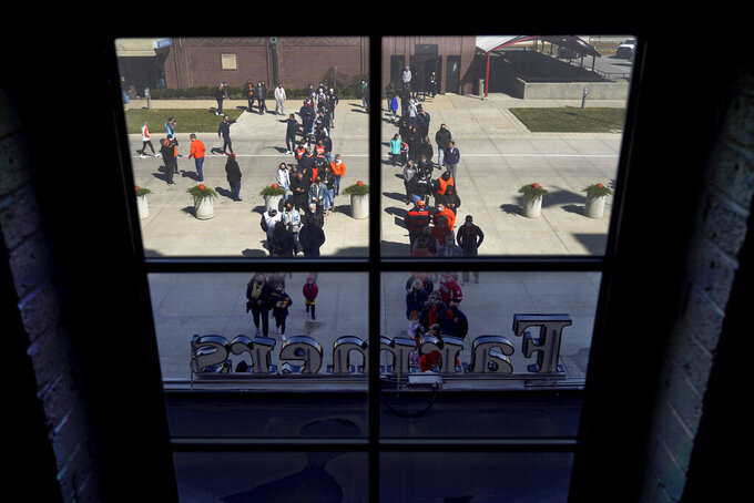 Basketball fans line up outside the Indiana Farmers Coliseum before a first round NCAA college basketball game between Illinois and Drexel Friday, March 19, 2021, in Indianapolis. (AP Photo/Charles Rex Arbogast)