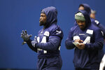 Seattle Seahawks running back Robert Turbin, left, stands near running back Marshawn Lynch, who looks over notes during warmups at the NFL football team's practice facility Tuesday, Dec. 24, 2019, in Renton, Wash. (AP Photo/Elaine Thompson)