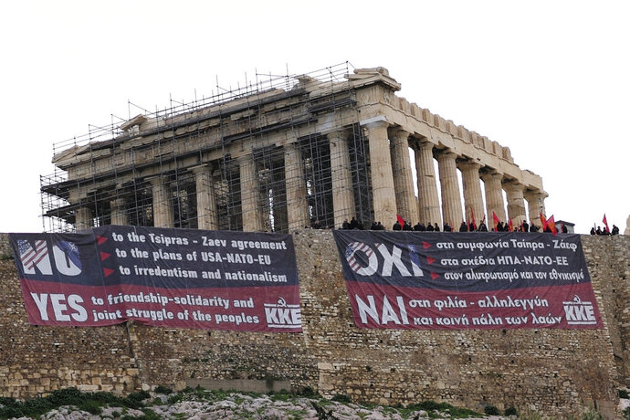 Members of Greece's Communist Party stand on the ancient Acropolis Hill over giant banners protesting against the Prespa Agreement in front of the ancient Parthenon temple, in Athens, Thursday, Jan. 24, 2019. Greek lawmakers are debating a historic agreement aimed at normalizing relations with Macedonia in a stormy parliamentary session scheduled to culminate in a Thursday vote, while opponents have announced a series of protests. (AP Photo/Petros Giannakouris)