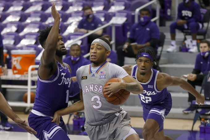 TCU guard Mike Miles (1) and guard RJ Nembhard (22) defend against Kansas guard Dajuan Harris (3) during the first half of an NCAA college basketball game in Fort Worth, Texas, Tuesday, Jan. 5, 2021. (AP Photo/Ron Jenkins)