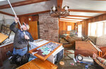 Steve O'Donnell works to open a skylight while standing in floodwaters inside a home Friday, March 22, 2019, in Bellevue, Neb. Flooding in Nebraska has caused an estimated $1.4 billion in damage. The state received Trump's federal disaster assistance approval on Thursday. (Kent Sievers/Omaha World-Herald via AP)