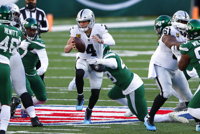 Las Vegas Raiders quarterback Derek Carr (4), center, tries to avoid the New York Jets defense during the first half an NFL football game, Sunday, Dec. 6, 2020, in East Rutherford, N.J. (AP Photo/Noah K. Murray)