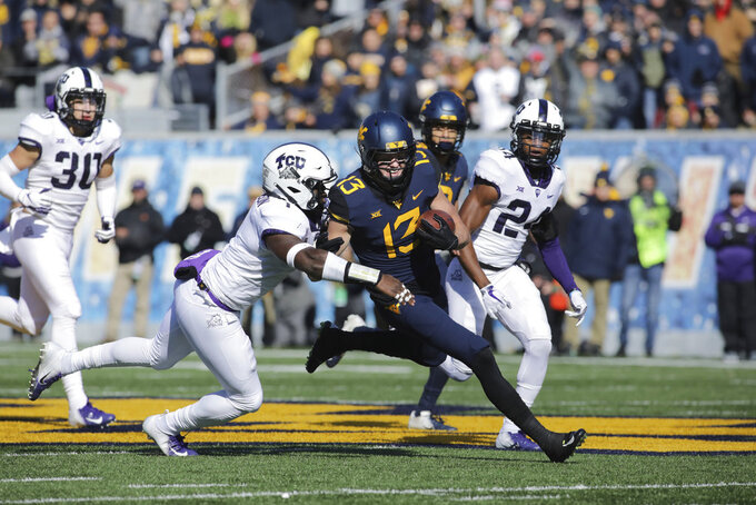 West Virginia wide receiver David Sills V (13) is tackled by TCU linebacker Jawuan Johnson , left,  during the first half of an NCAA college football game Saturday, Nov. 10, 2018, in Morgantown, W.Va. (AP Photo/Raymond Thompson)
