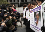 Participants pay a silent tribute as they hold pictures of the deceased Kim Bok-dong, one of the many former South Korean sex slaves who were forced to serve for the Japanese military in World War II, during a weekly rally near the Japanese Embassy in Seoul, South Korea, Wednesday, Jan. 30, 2019. Hundreds of South Koreans are mourning the death of a former sex slave for the Japanese military during World War II by demanding reparations from Tokyo over wartime atrocities. (AP Photo/Lee Jin-man)