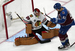 Chicago Blackhawks goaltender Marc-Andre Fleury, left, stops a shot off the stick of Colorado Avalanche left wing Gabriel Landeskog in the first period of an NHL hockey game Wednesday, Oct. 13, 2021, in Denver. (AP Photo/David Zalubowski)